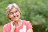 Portrait of an attractive middle-aged woman in a red dress — Stock Photo