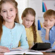 Children with the tablet and books — Stock Photo