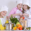 Three cheerful girls cooking — Stock Photo