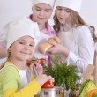 Three cheerful girls cooking — Stock Photo #30736115
