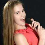 Girl singing on a black background — Stock Photo