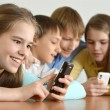 Cheerful kids with a mobile — Stockfoto