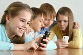 Cheerful kids with a mobile — Stock Photo