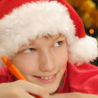 Boy in santa hat writing — Stock Photo
