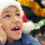 Good Caucasian teenager in a santa hat draws — Stock Photo #30999751