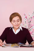 Pretty Caucasian aged woman sitting with a magazine — Stock Photo