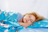 Attractive older woman resting in the bedroom — Stock Photo