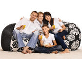 Family watching tv sitting on cushions — Stock Photo