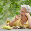 Elderly man reading book and drinking wine — Stock Photo