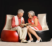 Elderly couple reading on armchairs — Stock Photo