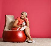 Senior woman resting in armchair — Stock Photo