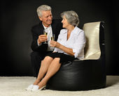 Elderly couple celebrating with champagne — Stock Photo