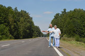 Senior couple hitchhiking — Stock Photo