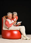 Elderly couple reading newspaper — Stock Photo