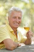 Elderly man drinking on nature — Stock Photo