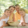 Happy family with a basket of fruit — Stock Photo #32065577