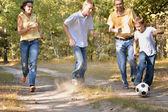 Família feliz jogar floresta futebol — Foto Stock