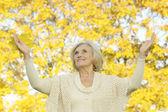 Happy senior woman in autumn park — Stock Photo