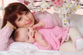 A beautiful happy mom with her daughter lying in bed — Stock Photo