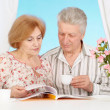 Amusing older couple resting in the bedroom — Stock Photo