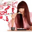 Stock Photo: Beautiful girl eating sushi