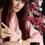 Beautiful girl eating sushi — Stock Photo #32394323