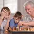 Two boys and grandfather playing chess — Stock Photo #32394347
