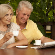 Beauteous older couple sitting on veranda — Stock Photo #32394613