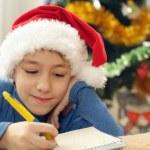 Good Caucasian teenager in a santa hat draws — Stock Photo #32394655
