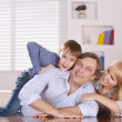 Family sitting on sofa at home — Stock Photo