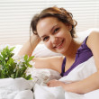 Nice Caucasian woman lying in a bed of flowers — Stock Photo