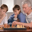 Stock Photo: Two boys and grandfather playing chess