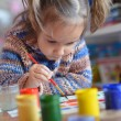 Beautiful little girl draws paint — Stock Photo