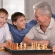 Two boys and grandfather playing chess — Stock Photo #32398409