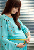 Pregnant woman holds hands a stomach — Stock Photo