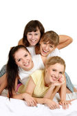 Four nice girls on the bed — Stock Photo