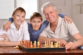 Happy family at a chess — Stockfoto