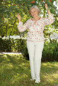 Mooie bejaarde vrouw in de tuin — Stockfoto