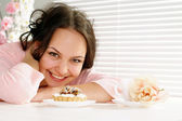 Beautiful happy woman is and looks at a cake — Stock Photo
