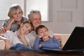 Two boys and grandparents with a laptop — Stock Photo