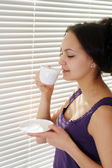 A beautiful Caucasian girl standing near a window with a cup — Stock Photo