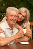 Good-looking older couple sitting on the veranda — Stock Photo