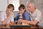 Two boys and grandfather playing chess — Stock Photo