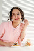 A pretty caucasian female sitting at the table with a cake — Stock Photo