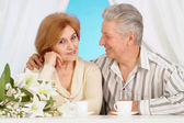 Nice older couple resting in the bedroom — Stock Photo