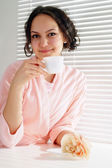 A beautiful caucasian girl sitting at the table with a cup — Stock Photo