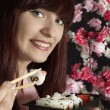 Beautiful girl eating sushi — Stock Photo