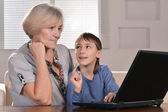 Boy and grandmother with laptop — Stock Photo