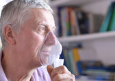 Elderly man doing inhalation — Stock Photo