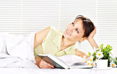 Woman lying in a bed of book — Stock Photo